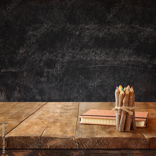 Poster vintage notebook and stack of wooden colorful pencils on wooden textures table