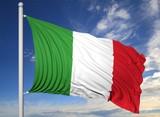 Waving flag of Italy on flagpole, on blue sky background.