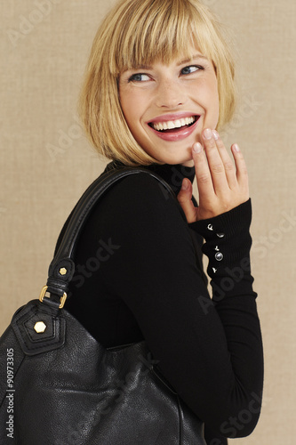 Happy young blond businesswoman laughing in studio © sanneberg