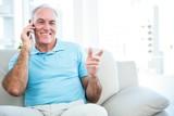 Senior happy man using smartphone while sitting on sofa