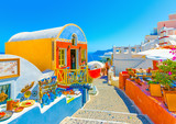 Typical colorful narrow street in Oia the most beautiful village of Santorini island in Greece - 91046948