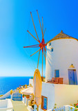 Amazing view to the sea including a pictorial old traditional windmill in Oia the most beautiful village of Santorini island in Greece