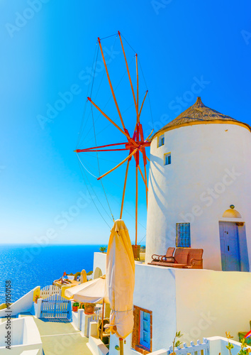 Fotobehang Santorini Amazing view to the sea including a pictorial old traditional windmill in Oia the most beautiful village of Santorini island in Greece