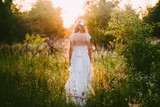 Stylish beautiful blonde bride standing in her wedding dress back to nature in the sunset light, wedding, marriage, tenderness, woman, lifestyle