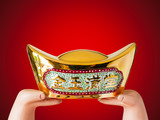 Hand over an antique Chinese golden money with wealthy wording on, to give wish well,rich,prosperity,happiness,affluent