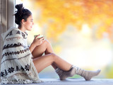 Fototapety Beautiful young smiling brunette woman with cup of coffee wearing knitted nordic print poncho sitting home by the window.. Blurred fall garden background.