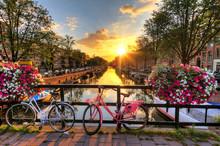 Mooie zonsopgang over Amsterdam, Nederland, met bloemen en fietsen op de brug in het voorjaar