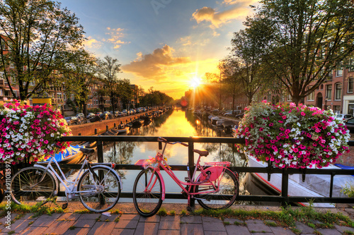 Zdjęcia na płótnie, fototapety na wymiar, obrazy na ścianę : Beautiful sunrise over Amsterdam, The Netherlands, with flowers and bicycles on the bridge in spring