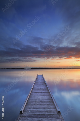 Naklejka Jetty on a lake at sunrise, near Amsterdam The Netherlands