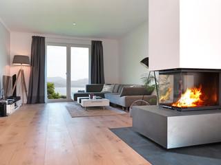 Wohnzimmer mit Kamin und Aussicht auf die Küste