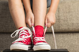 Fototapety Girl wearing a pair of red sneakers