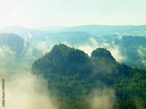 View into deep misty valley in Saxony Switzerland. Sandstone peaks increased from heavy colorful fog. - 91143907