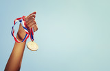 Fototapety woman hand raised, holding gold medal against sky. award and victory concept
