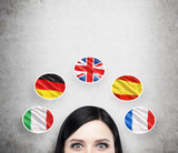 Fototapety A concept of foreign language studying process. A foreseen of the brunette girl surrounded by icons of european flags. Concrete background.