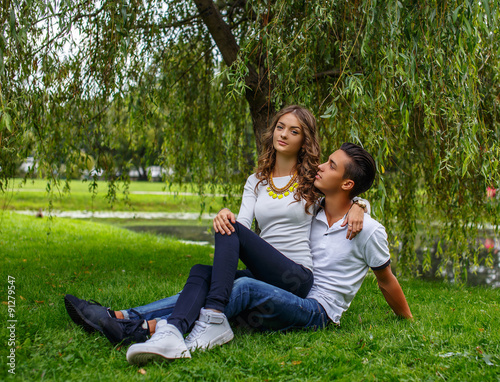 Beautiful young couple relaxing on grass field.