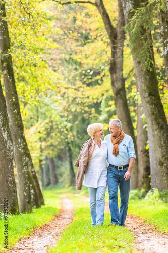 Fotobehang Zwavel geel Älteres Paar macht Spaziergang im Wald
