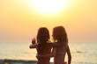 Two juvenile girls stare at sunset