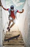 Fototapety Professional skateboarder boy jumps off the stairs