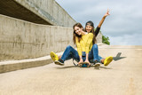 Fototapety Skateboarder girlfriends roll down the slope