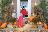 Children in Cape Costumes Trick-or-Treating on Halloween