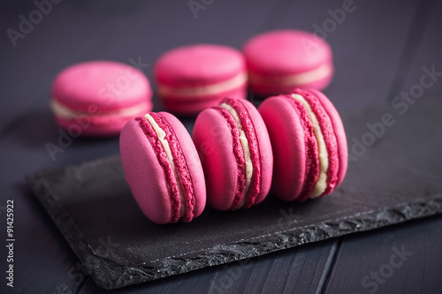 Foto op Aluminium Macarons Pink raspberry macaroons on black background