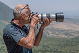 Man photographing Rift Valley with long lens poster