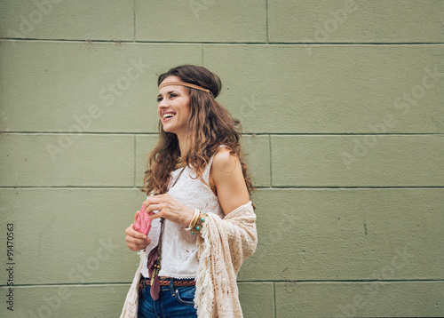 Poster Happy trendy hipster woman standing against wall outdoors