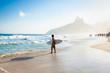 Quadro Brazilian surfer walking with surfboard toward Two Brothers Moun