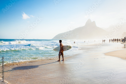 Papiers peints Rio de Janeiro Brazilian surfer walking with surfboard toward Two Brothers Moun