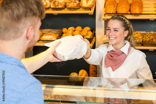 Shopkeeper in bakery hand bag of bread to customer