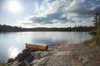 Orange canoe on rocky shore of Boundary Waters lake near sundown