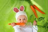 Fototapety Baby in rabbit hat eating carrot