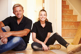 Man and woman sitting on floor during house refurbishment poster