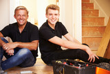 Two men sitting on wooden floor during a house refurbishment poster