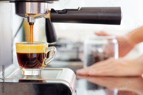 Poster Espresso coffee machine in kitchen. Coffee pouring into cup
