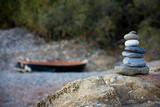 Pietre sovrapposte in riva al mare e barca sullo sfondo