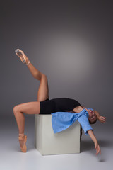 Young beautiful modern style dancer posing on a studio