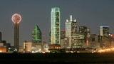 Slow pan of city lights illuminating the Dallas skyline at night.