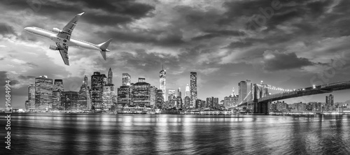 Black and white view of airplane overflying New York City - 91684994