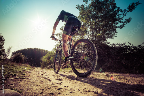 Poszter Man riding on a dirty road on a mountain bike