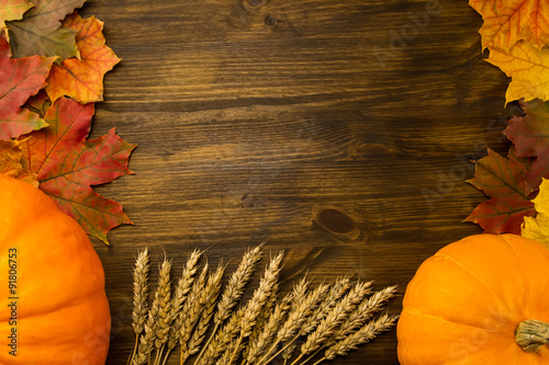 Yellow ripe pumpkin, maple leaves, red apples, wheat on wooden background. Thanksgiving, autumn, homemade.