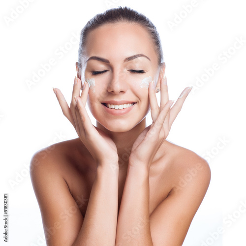 Poster beautiful model applying cosmetic cream treatment on her face on white