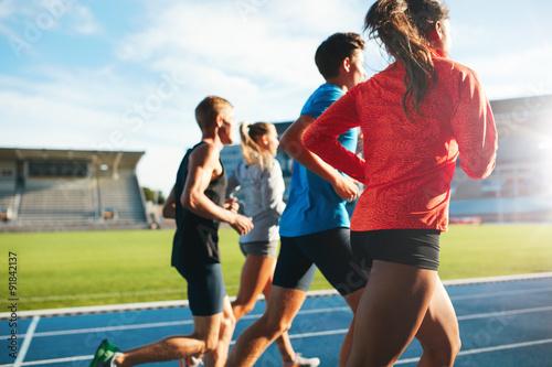 Valokuva Young athletes running on race track in stadium