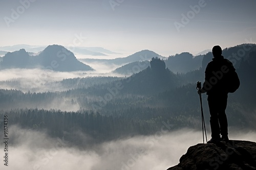 Keuken foto achterwand Nieuw Zeeland Dark silhouette of hiker with poles in hand. Sunny spring daybreak in rocky mountains. Hiker with sporty backpack stand on rocky peak above valley.