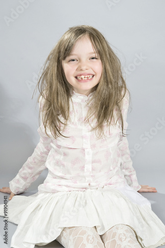 Poster Portrait of a disheveled five year old girl sitting on the floor