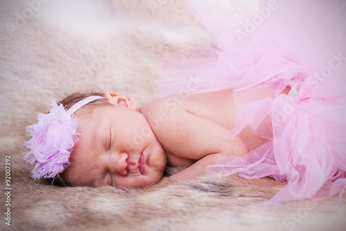 Fototapeta New born baby wearing a pink head band and tutu.