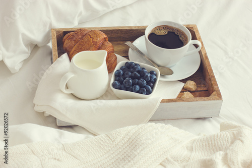 Poster cup of coffee, croissant and fresh blueberry on wooden tray, bre