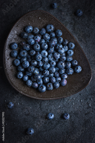 Poster Fresh blueberry on black plate with water drops