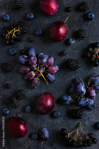 Poster fresh dark fruits and berries on black background.