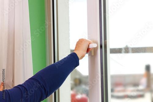 Poster Hand am Fenstergriff - Frauenhand öffnet das Fenster